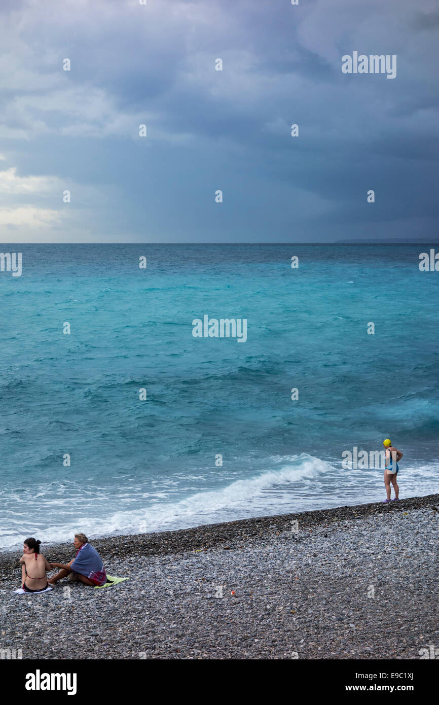Female swimmers on shingle beach during bad weather with rainstorm approaching over the sea - Stock Image