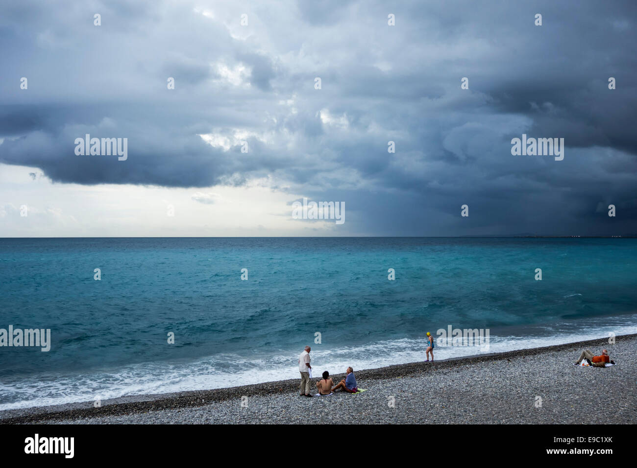 Female swimmers and sunbathers sitting on shingle beach during bad weather with rainstorm approaching over the sea - Stock Image