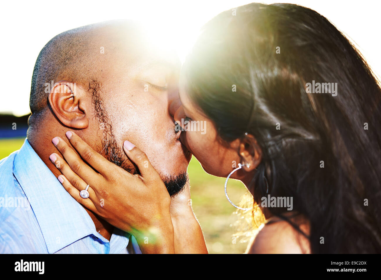 Couple kissing with womens hand on mans face showing diamond ring with the sun behind them setting - Stock Image