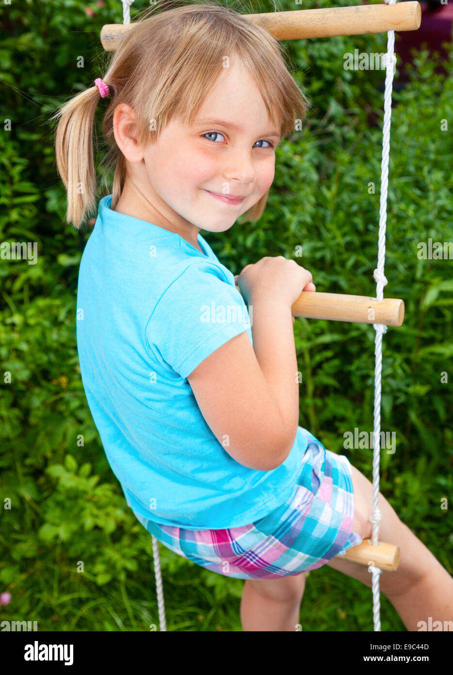 portrait of cute little girl playing at monkey bars stock photo