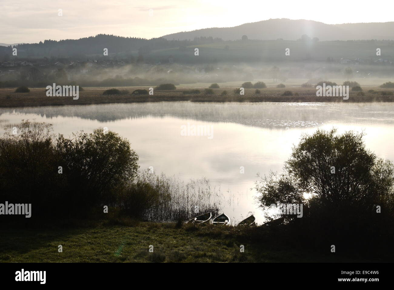 Boats Silence silent morning scenery with fog and mist at Lac de Remoray near Lac de Saint Point, Pontarlier, France Stock Photo