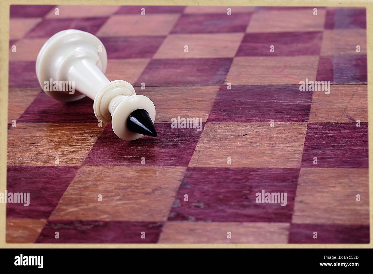 The defeat chess king against an old chessboard. - Stock Image