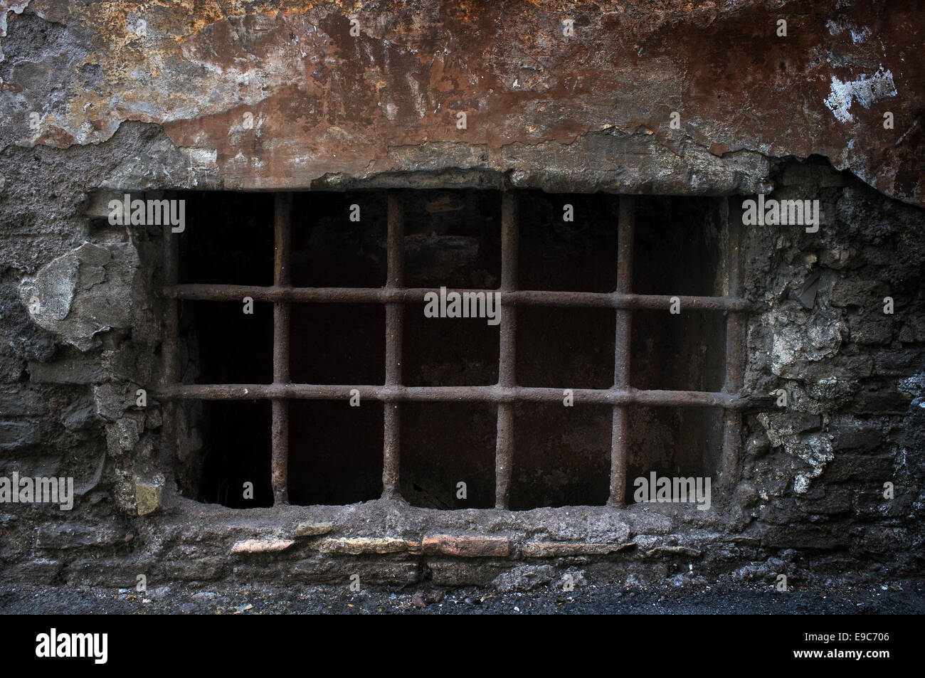 Old creepy cellar window with bars. - Stock Image