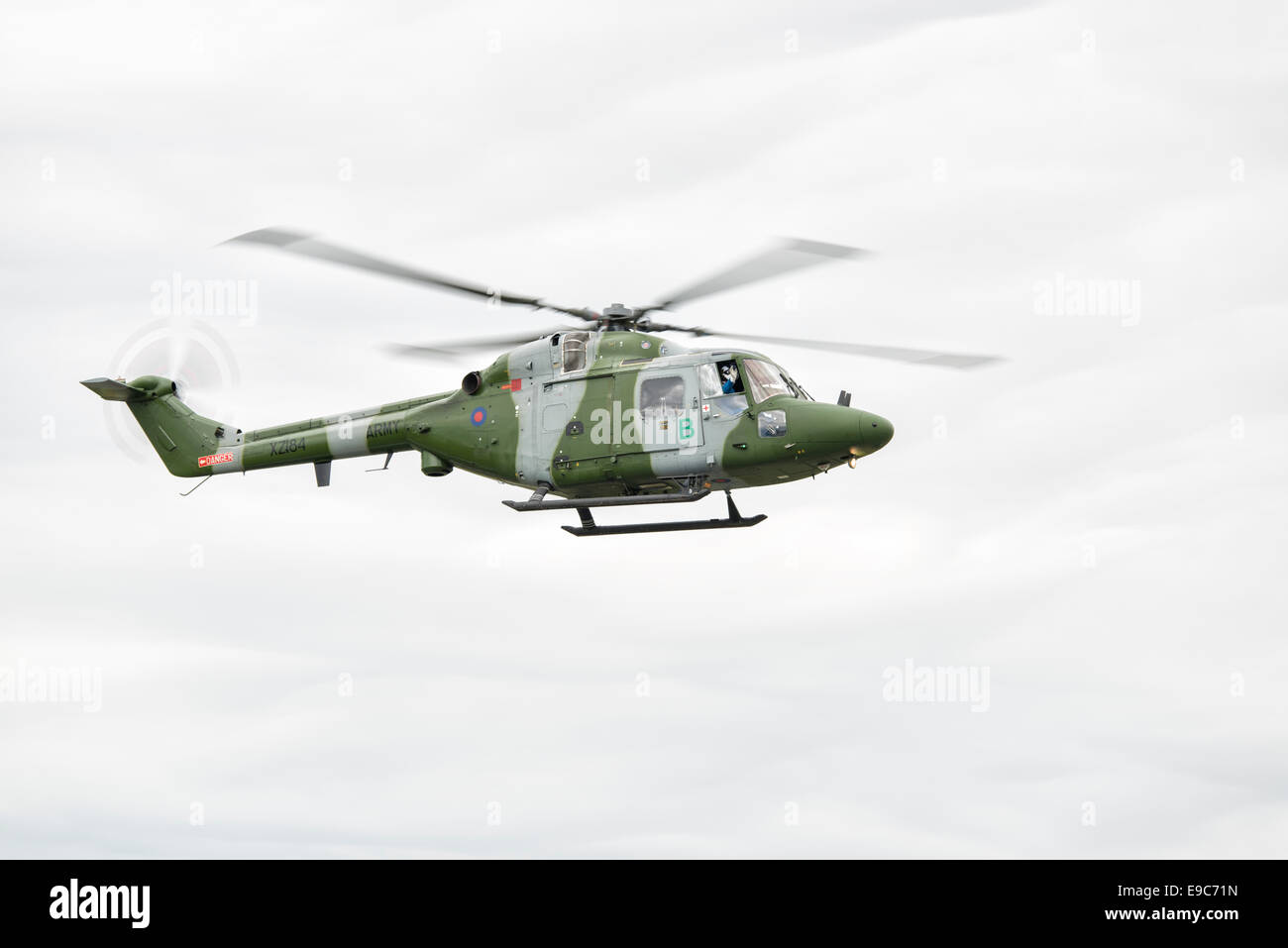 The pilot of this British Army Westland Lynx helicopter waves to the crowd during his display at the 2014 RIAT - Stock Image
