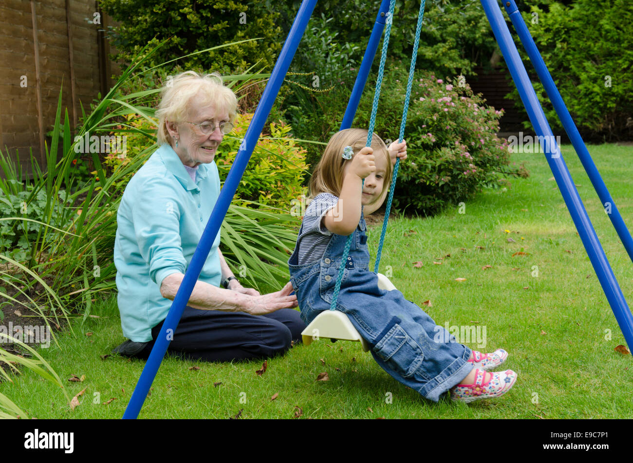 Great-grandmother playing with her great-granddaughter in a garden. UK - Stock Image
