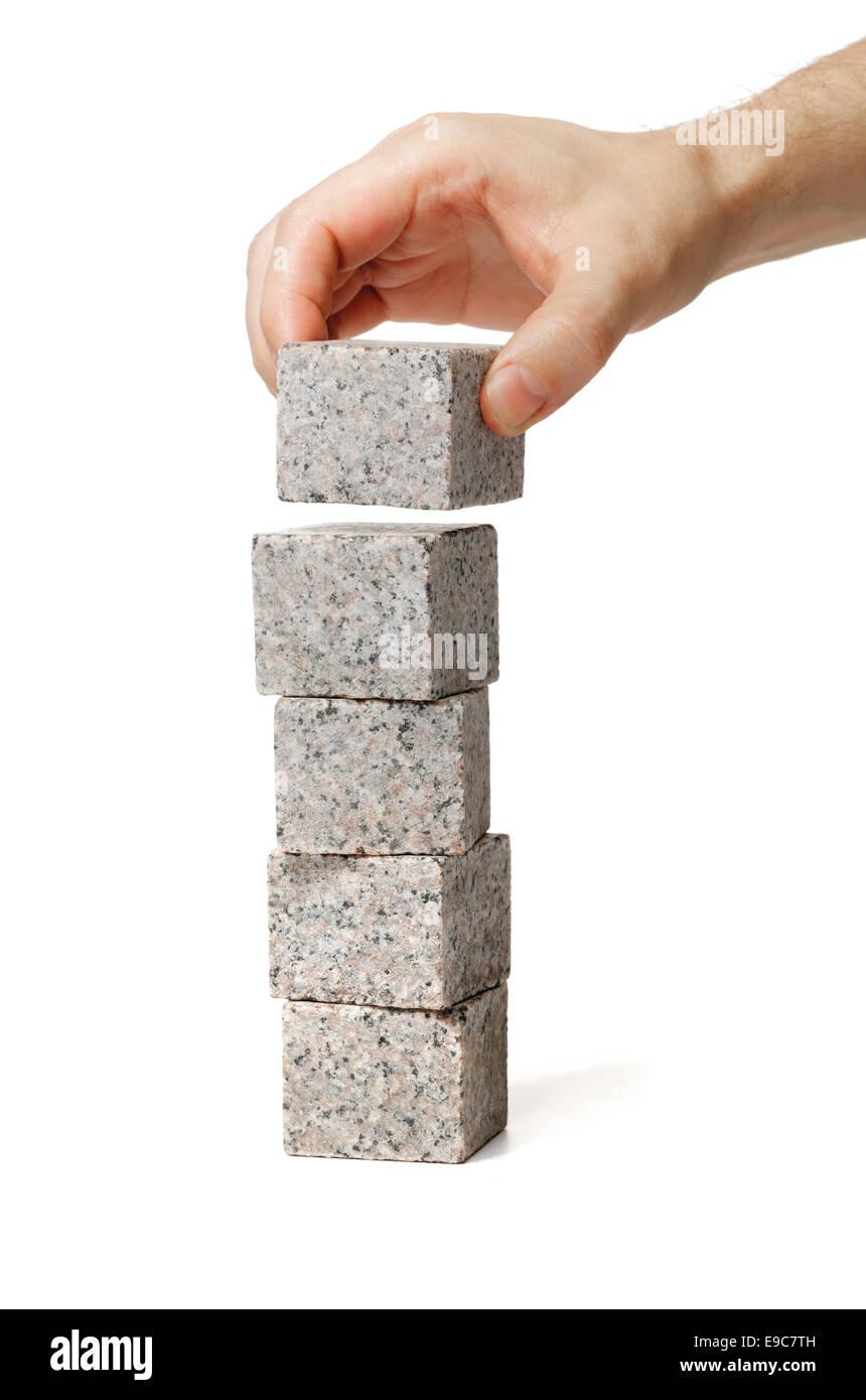 Man stacking small blocks of granite rock. - Stock Image