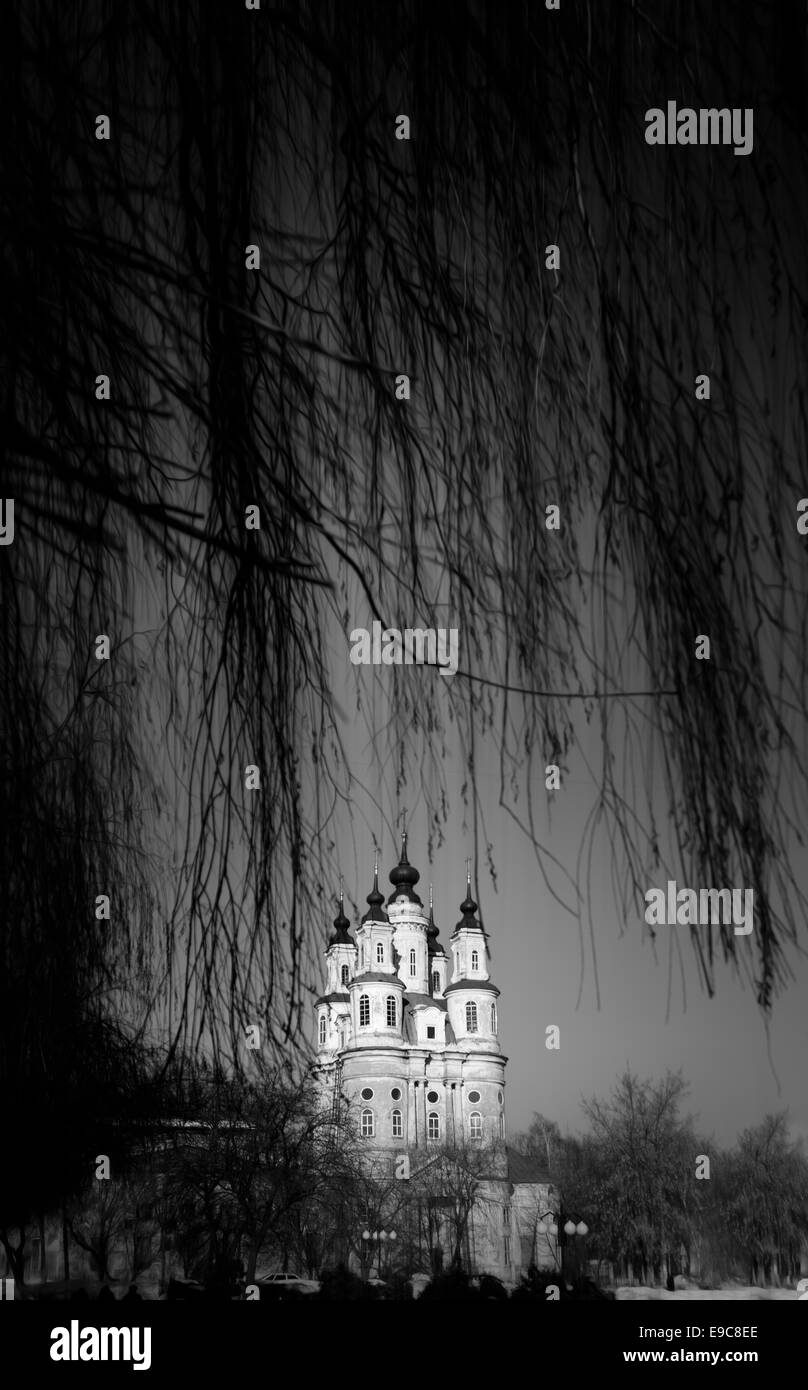 Black and white photo of beautiful Orthodox church with five domes through branches of tree. Winter nature. Kaluga, - Stock Image