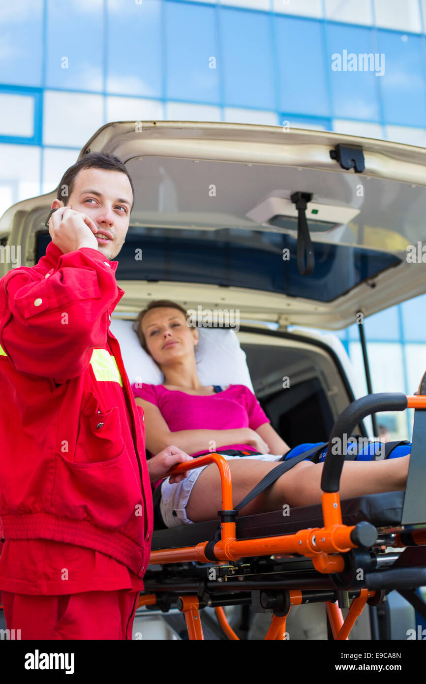 Paramedic taking care of a female patient - calling a hospital - Stock Image