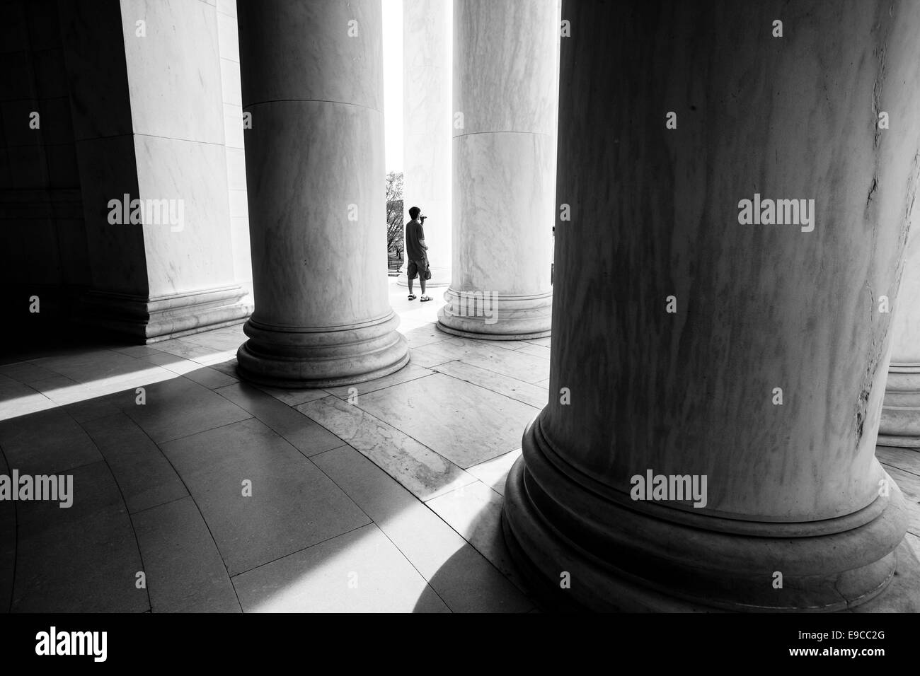 A boy stands silhouetted between the massive marble columns of the Jefferson Memorial in Washington, DC. - Stock Image