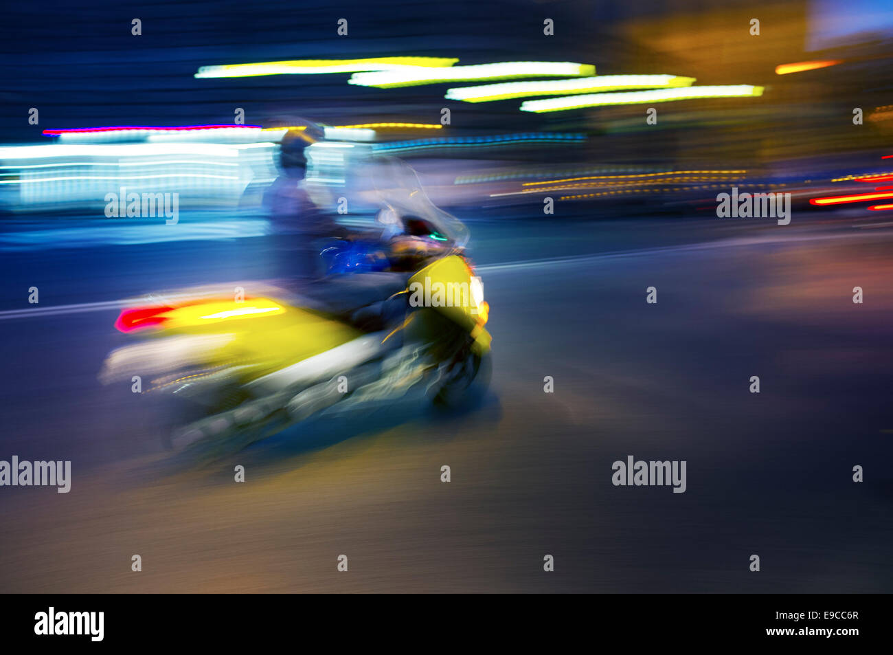 Abstract blurry image of a scooter driving at night. - Stock Image
