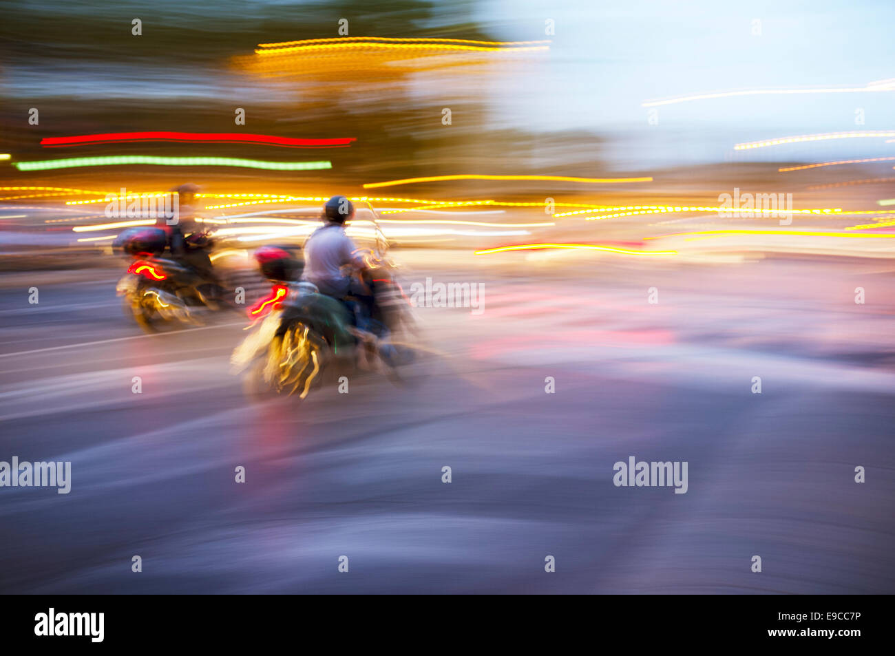 Abstract blurry image of a scooters driving at night. - Stock Image