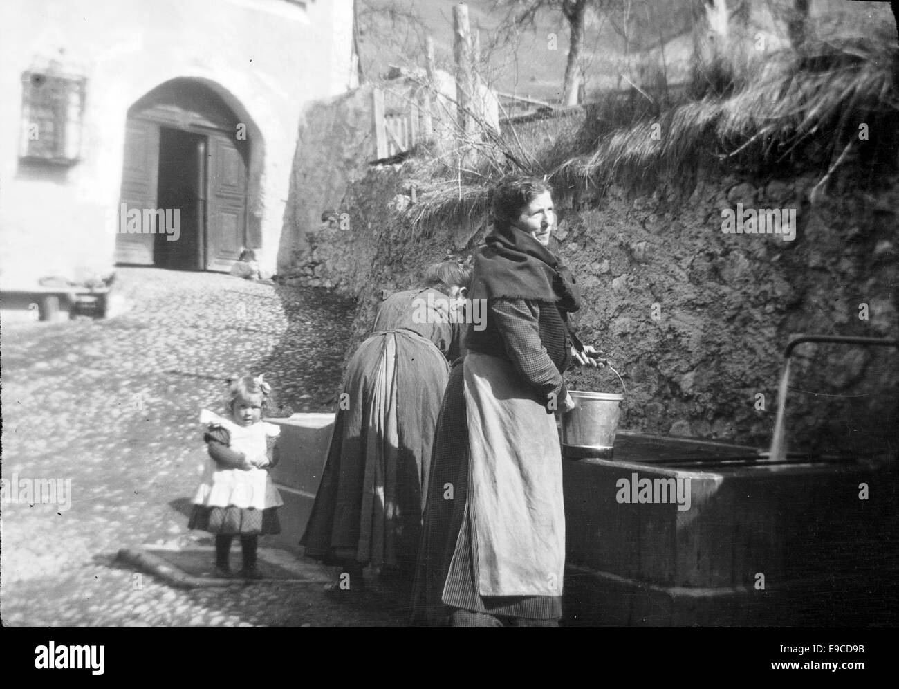 Women and a child at a well. Switzerland - Stock Image