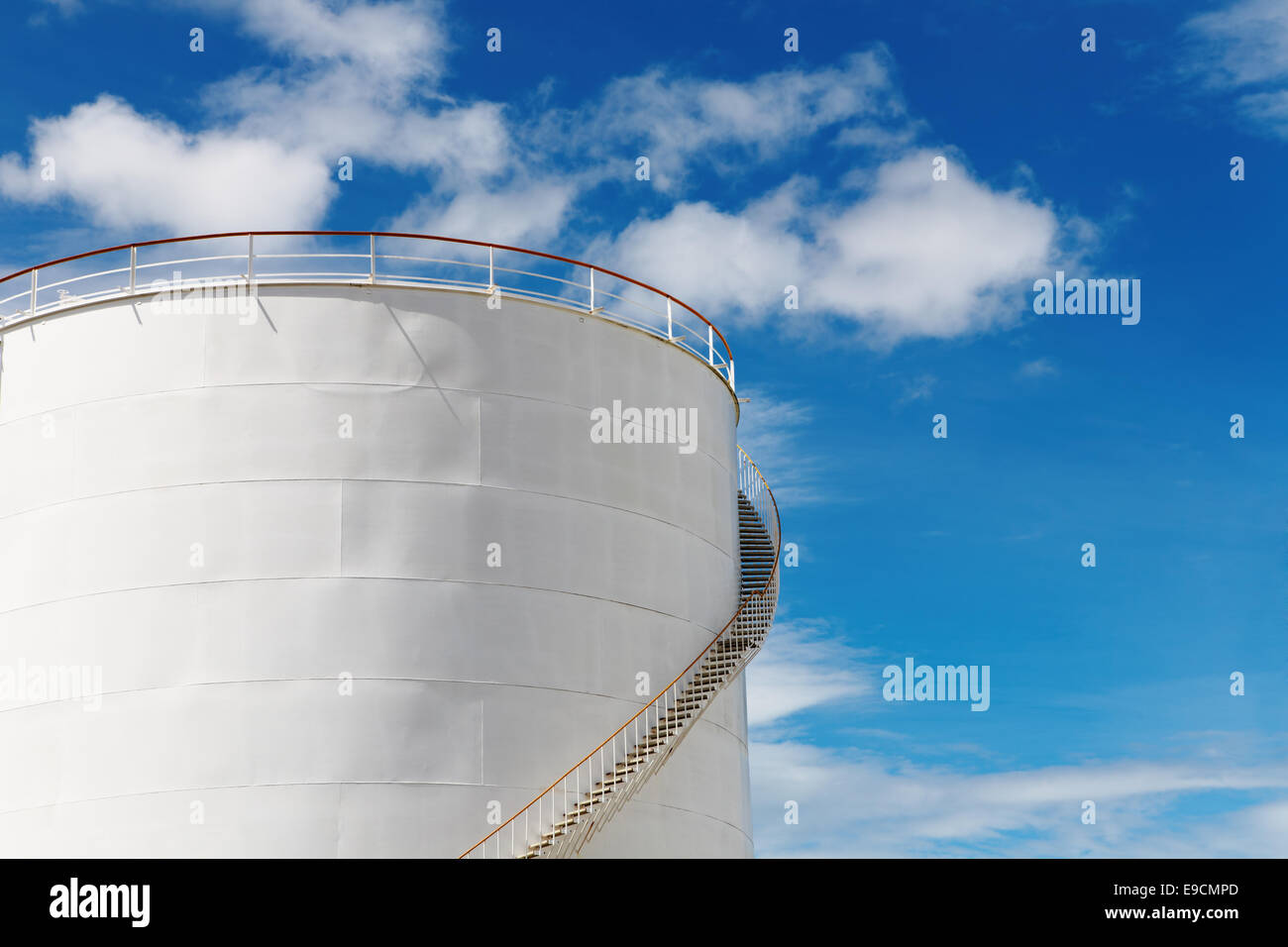 Industrial fuel tank against blue sky background - Stock Image