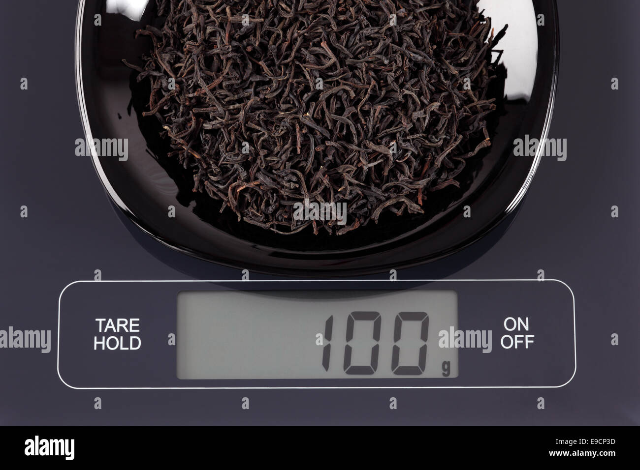 Black tea leaves in a black plate on digital scale displaying 100 gramme. Stock Photo