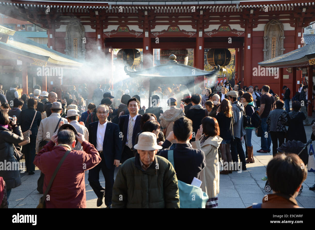 TOKYO, JAPAN - NOV 21: Buddhists gather around a fire to light incense and pray at Sensoji Temple on November 21, - Stock Image