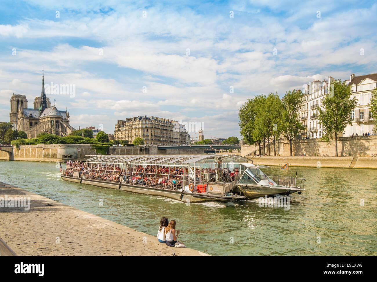 excursion boat on the river seine, in the background ile de la cite with  notre dame cathedral,  paris, ile de france, - Stock Image