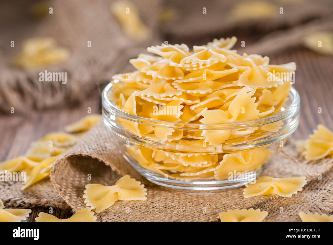 Farfalle (commonly known as Bow-Tie Pasta) in a bowl on wooden background - Stock Image