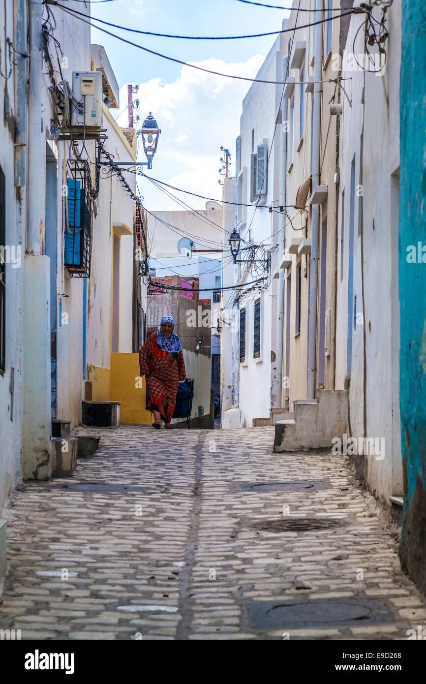 Elderly Arab woman walks along a narrow cobbled sidestreet  in the medina in Sousse,Tunisia. Stock Photo