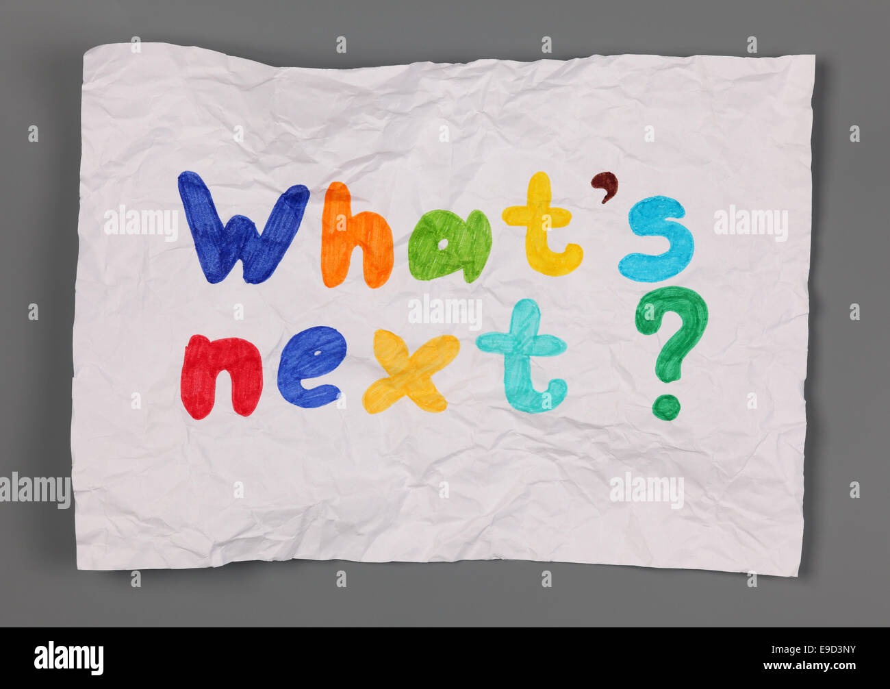 Crumpled paper with phrase 'What's next?' on gray background. - Stock Image