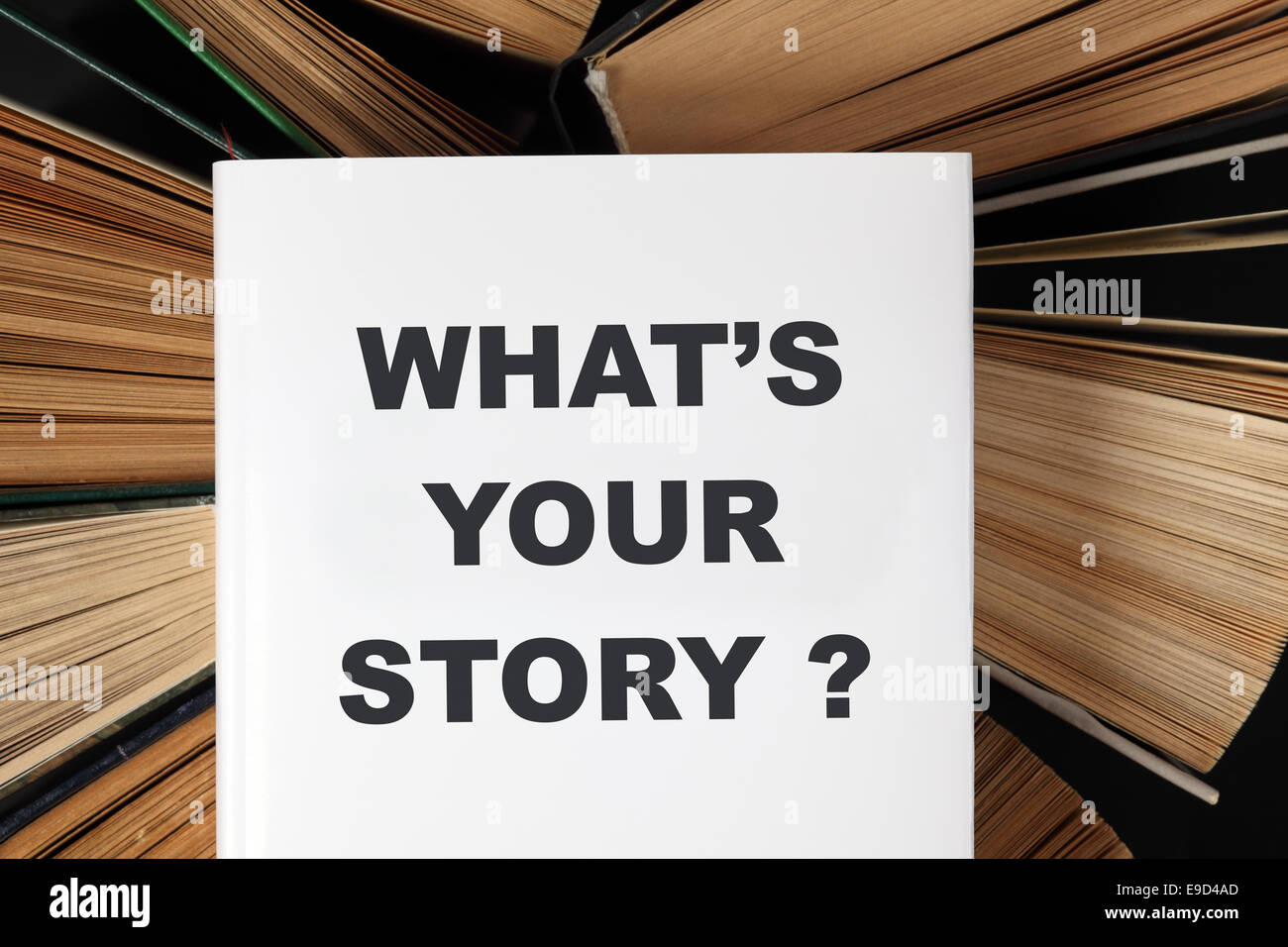 Top view of old hardback books with book 'What's your story?' - Stock Image