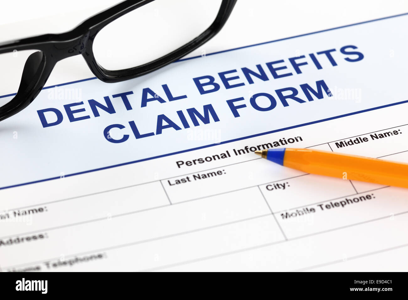 Dental benefits claim form with glasses and ballpoint pen. - Stock Image