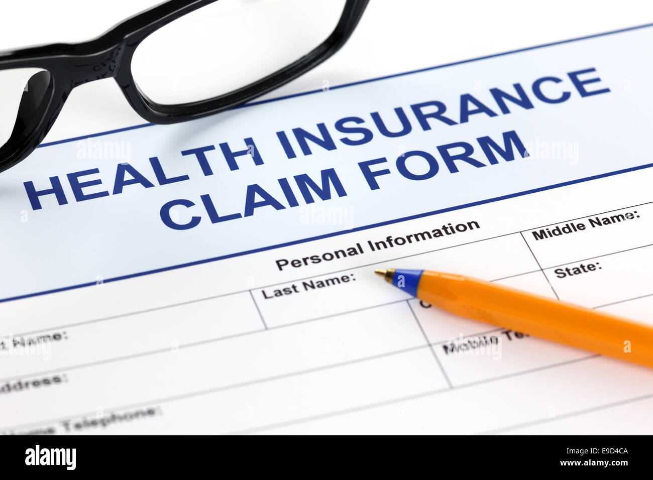 Health insurance claim form with glasses and ballpoint pen. - Stock Image