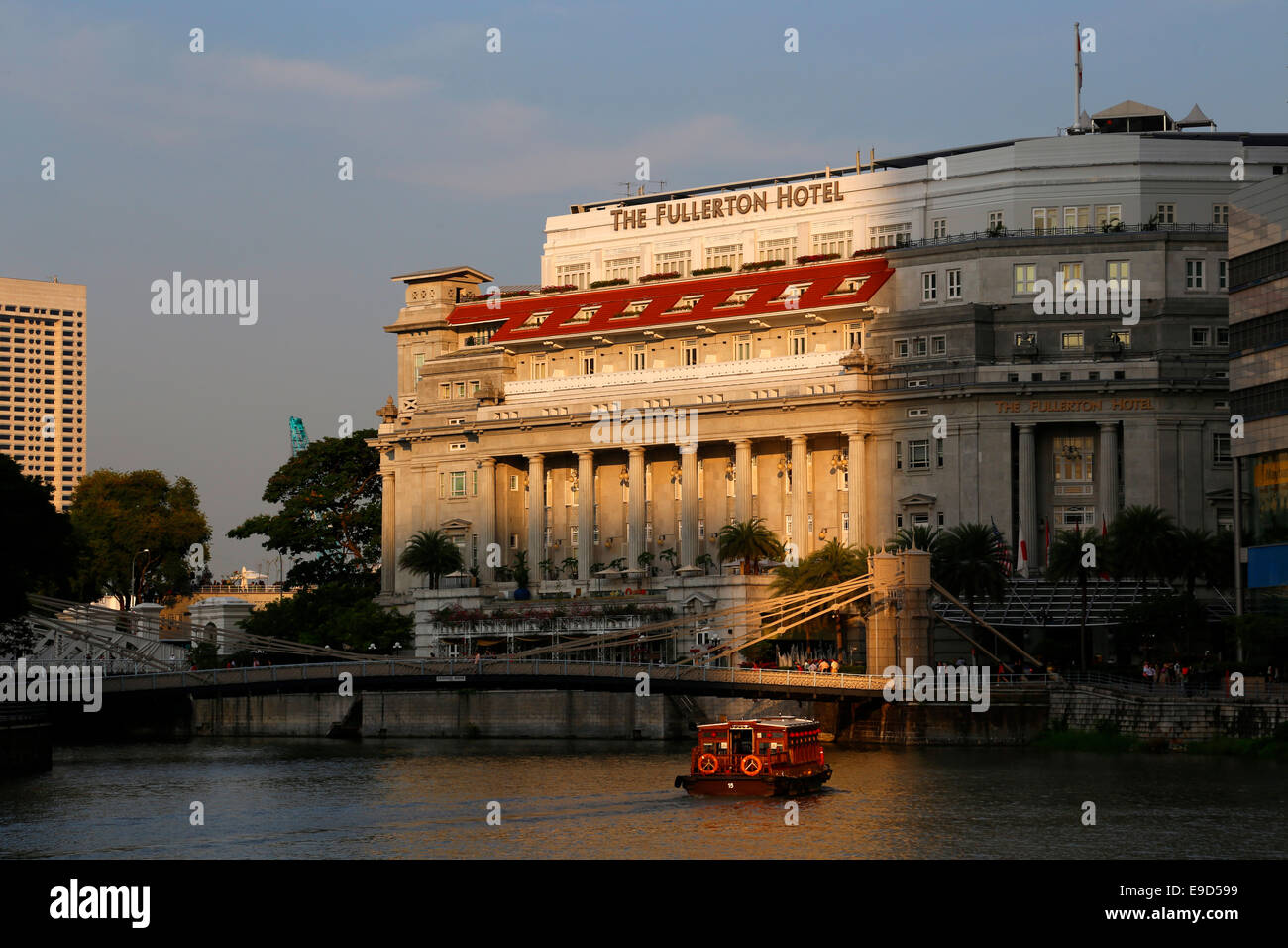 Singapore River with Cavenagh Bridge and the Fullerton Hotel behind, Colonial District, Singapore - Stock Image