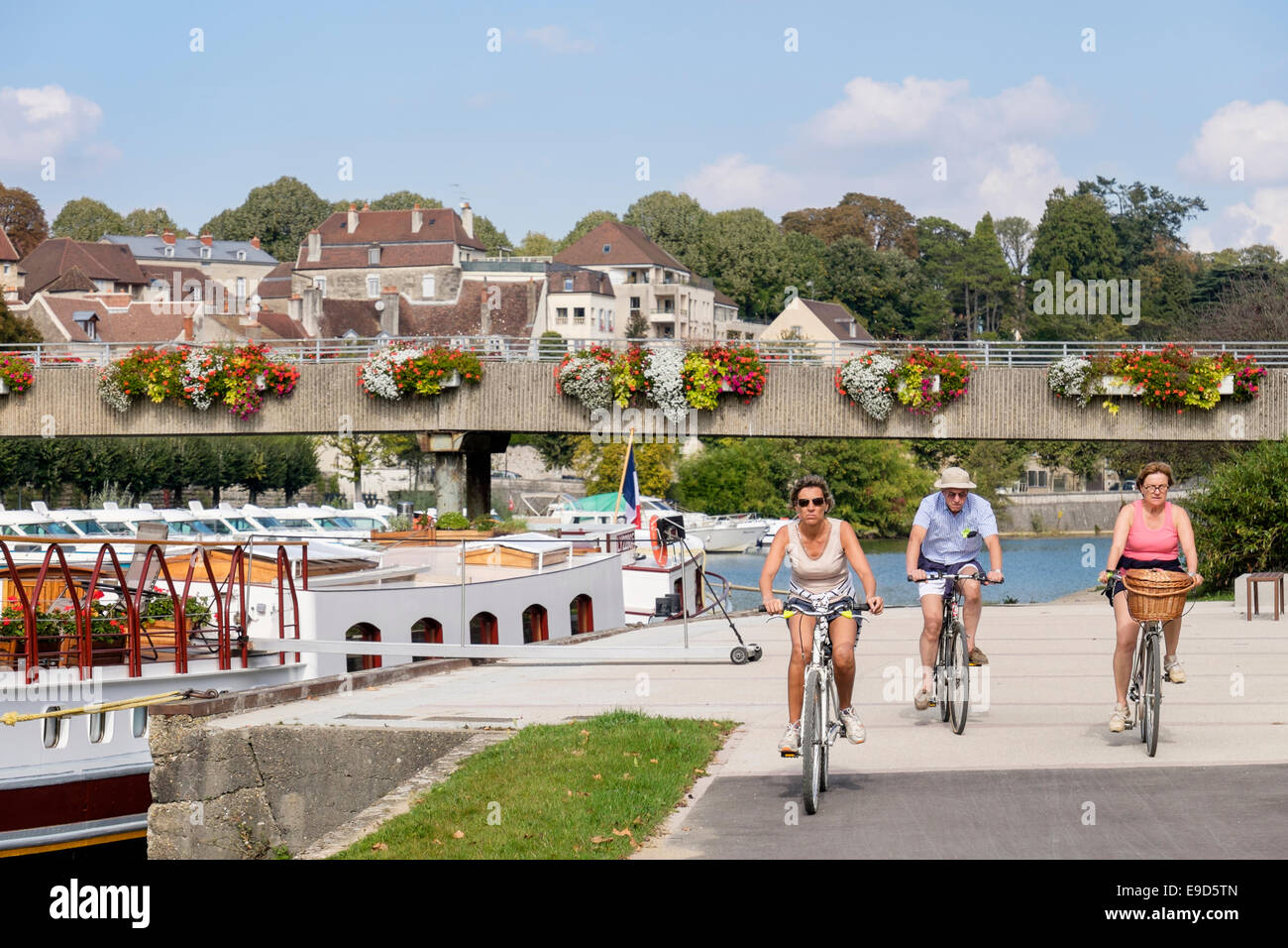 People cycling along riverside path by Canal du Rhone au Rhin and River Doubs. Dole, Jura, Franche-Comte, France, - Stock Image