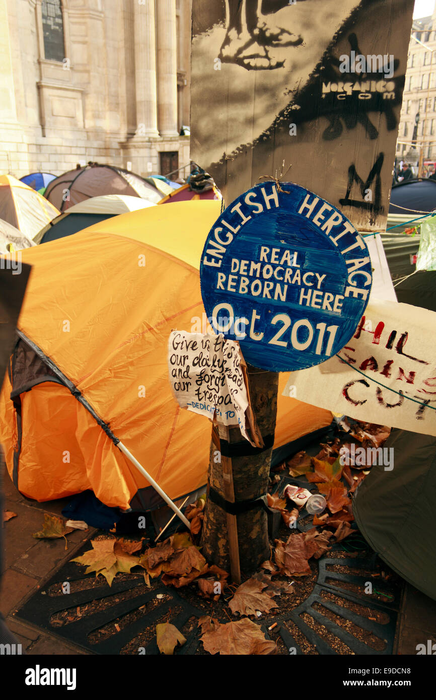 Democracy banner tied up to a tree near tents by Occupy London protesters opposite St.Paul's Cathedral in London, - Stock Image