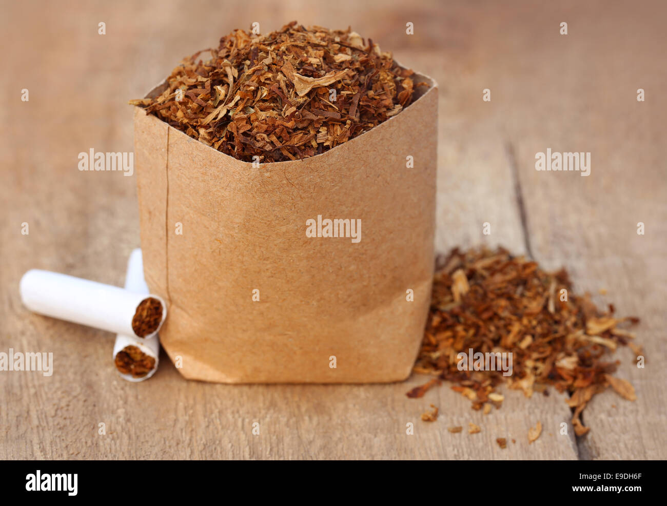 Dried tobacco leaves with cigarette on wooden surface - Stock Image