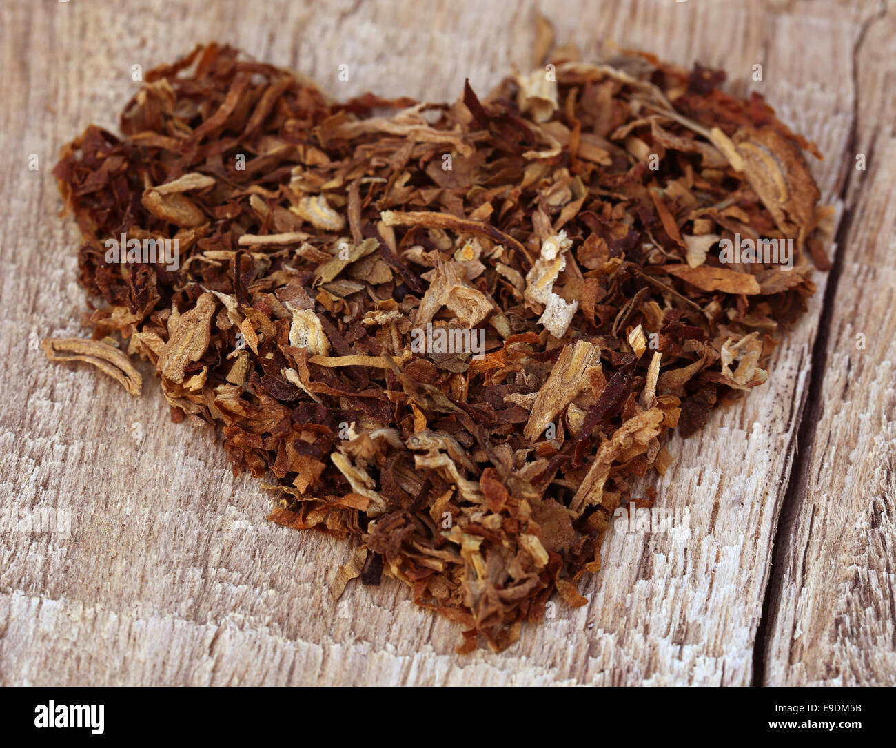 Dried tobacco leaves  decorated in heart shape on wooden surface - Stock Image