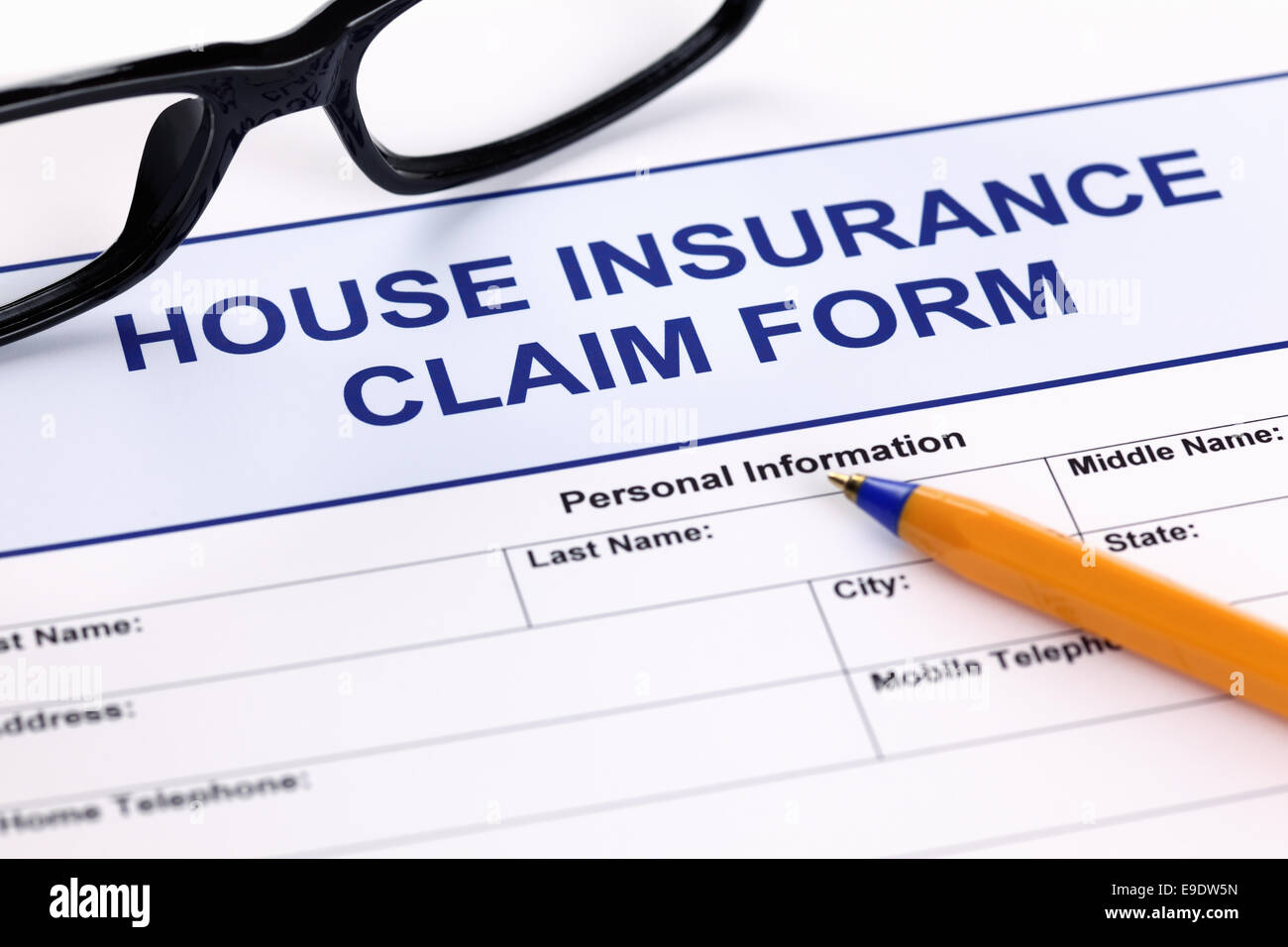 House insurance claim form with glasses and ballpoint pen. - Stock Image