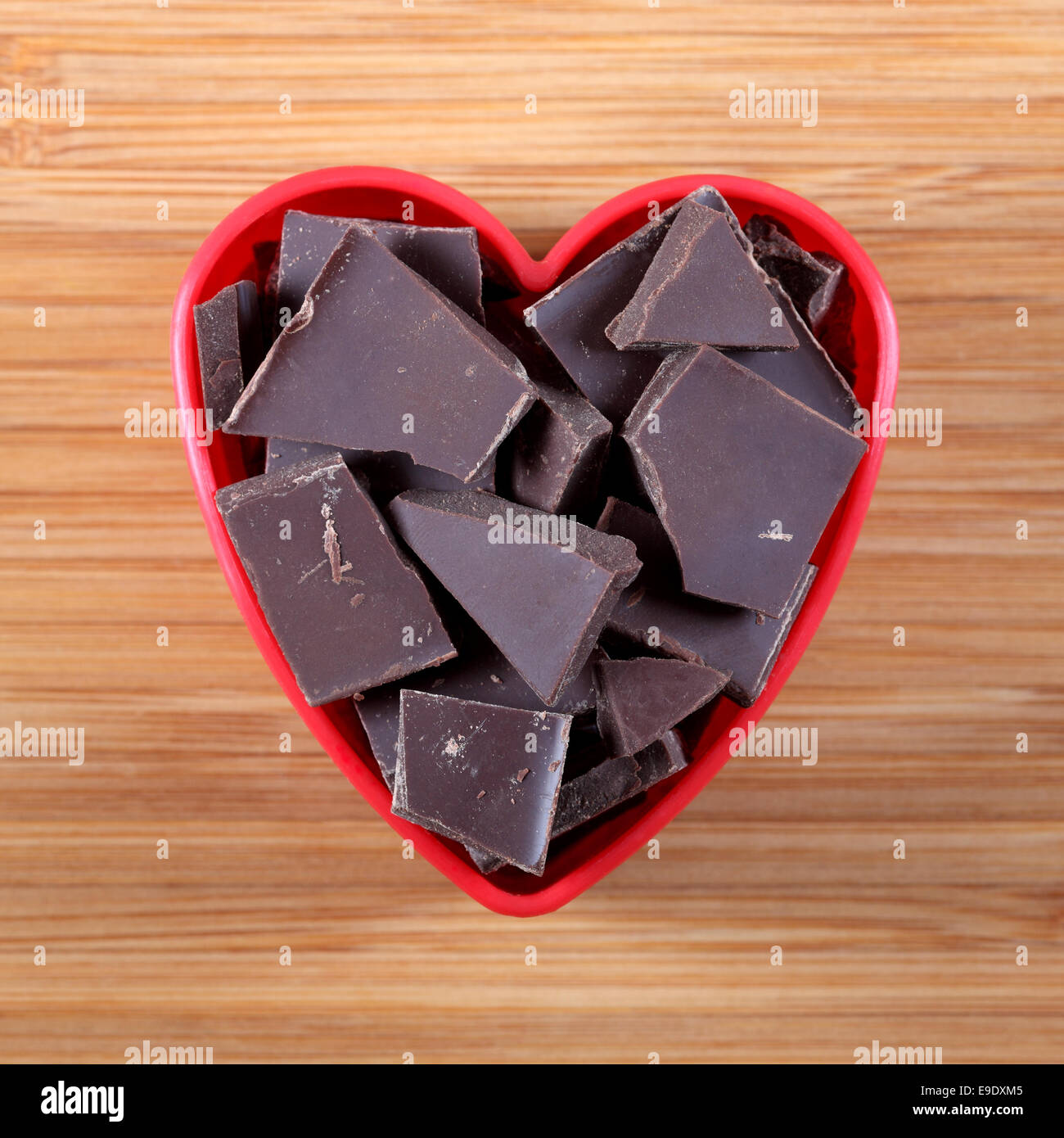Pieces of dark chocolate in a heart bowl. - Stock Image