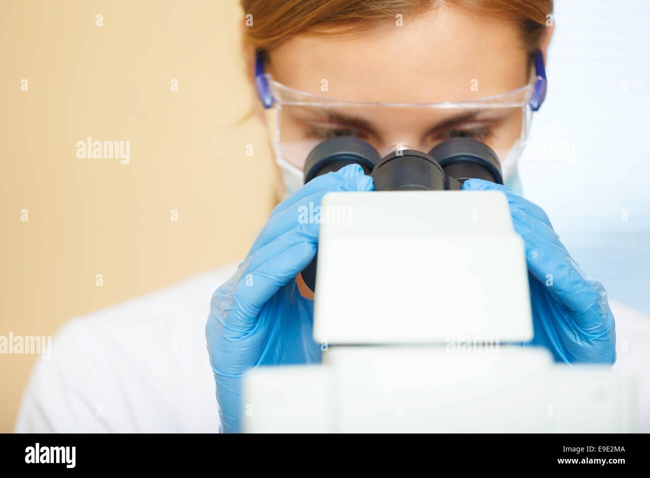 Beautiful woman in a laboratory working with a microscope. - Stock Image