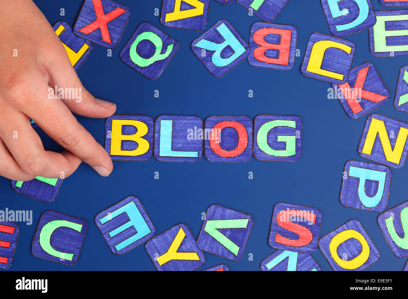 Word 'Blog' spell out on blue background with woman's hand and letters. Letters drawn by me. - Stock Image