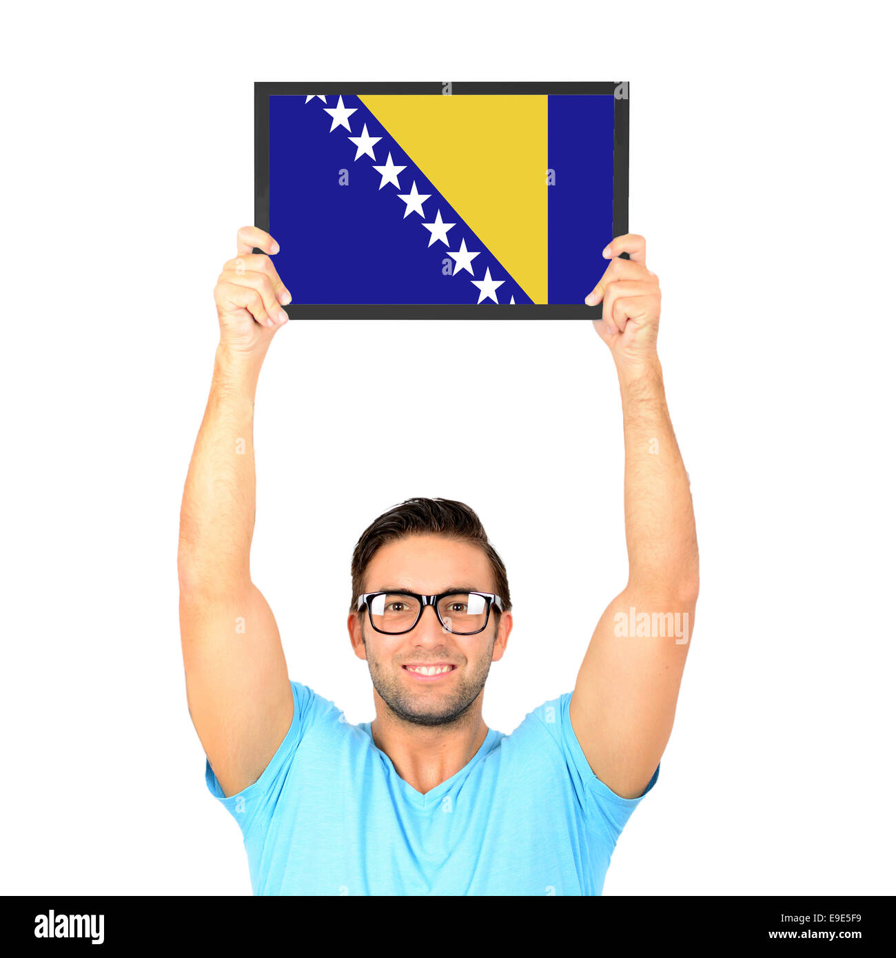 Portrait of a young casual man holding up board with National flag of Bosnia and Herzegovina - Stock Image