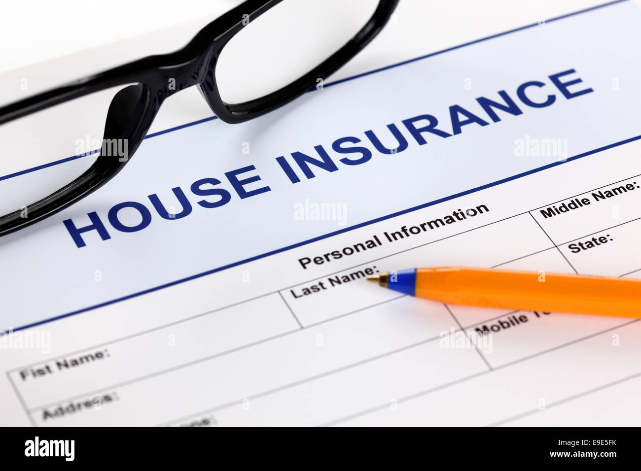 House insurance application form with glasses and ballpoint pen. - Stock Image