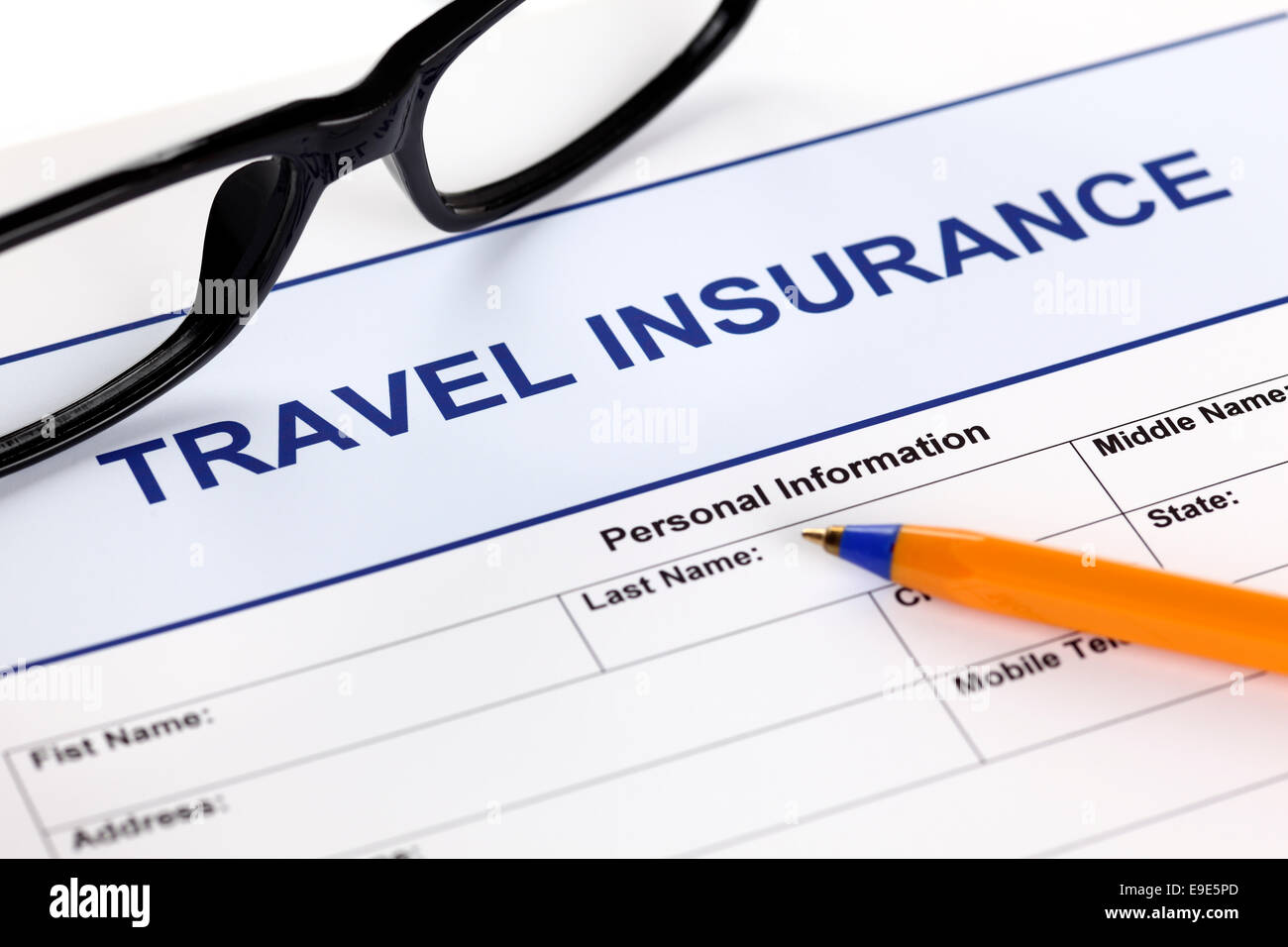 Travel insurance form with glasses and ballpoint pen. - Stock Image