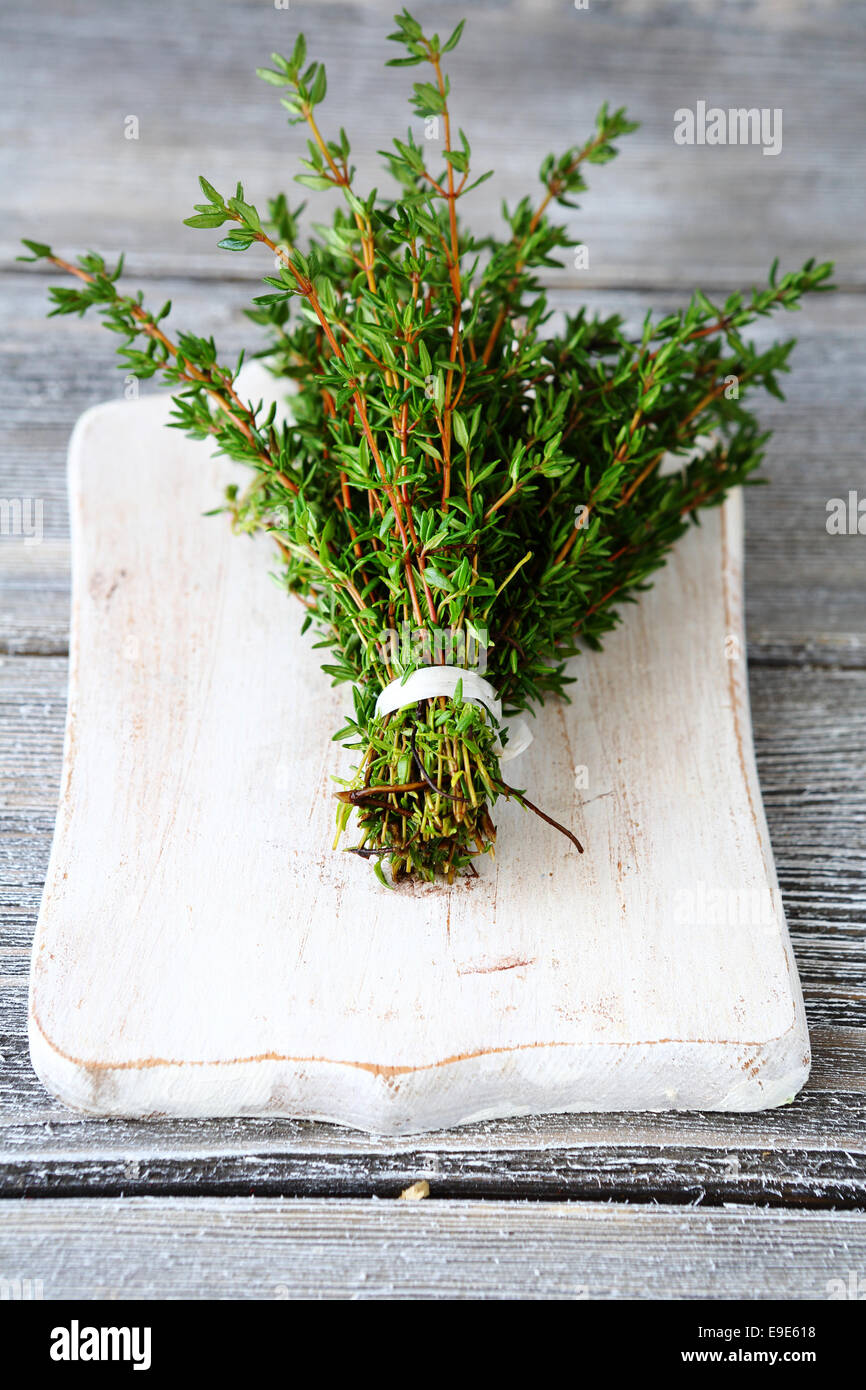 Fragrant thyme on cutting board, wooden background - Stock Image