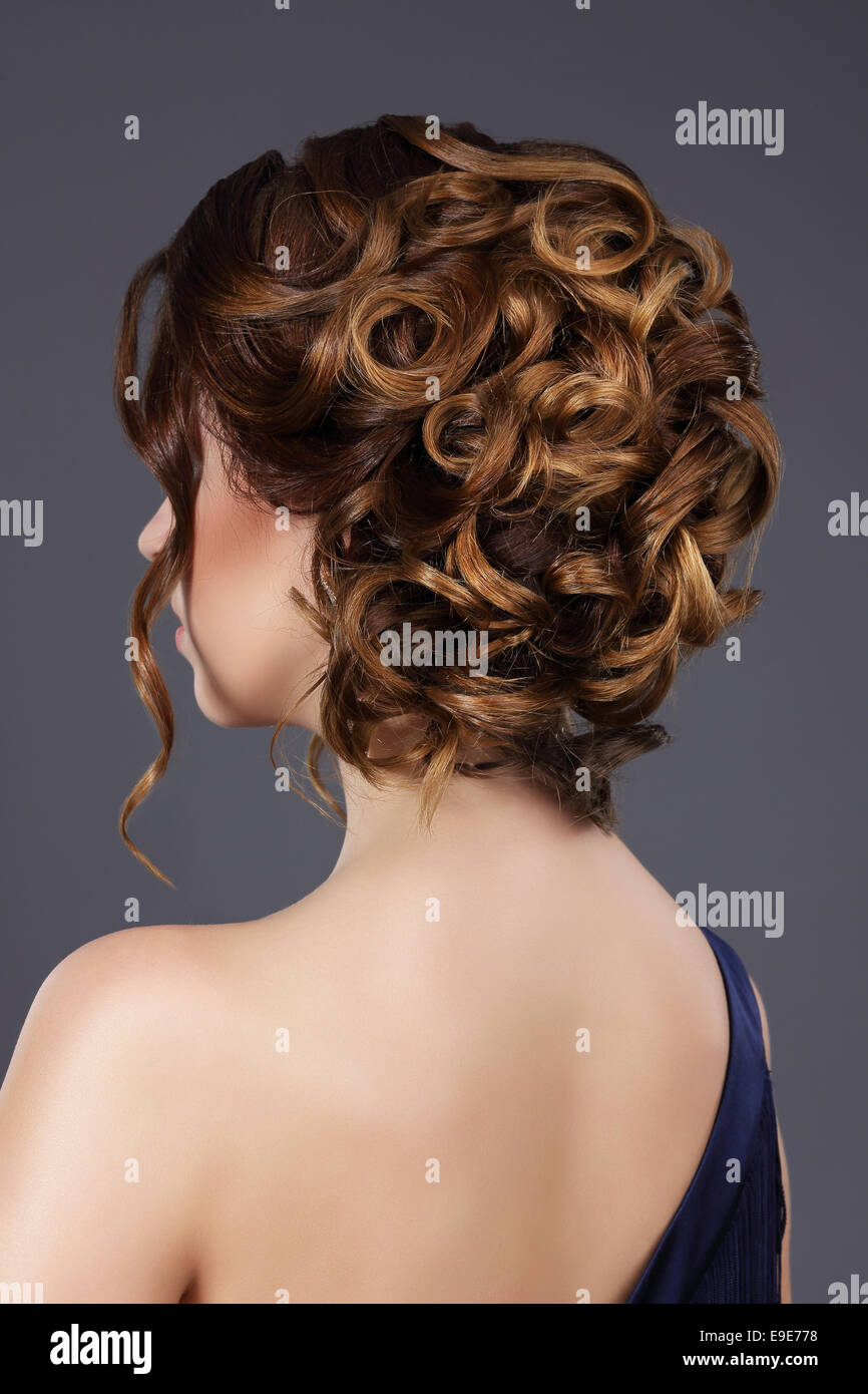 Rear View of Woman's Festive Hairstyle. Waved Hairs - Stock Image