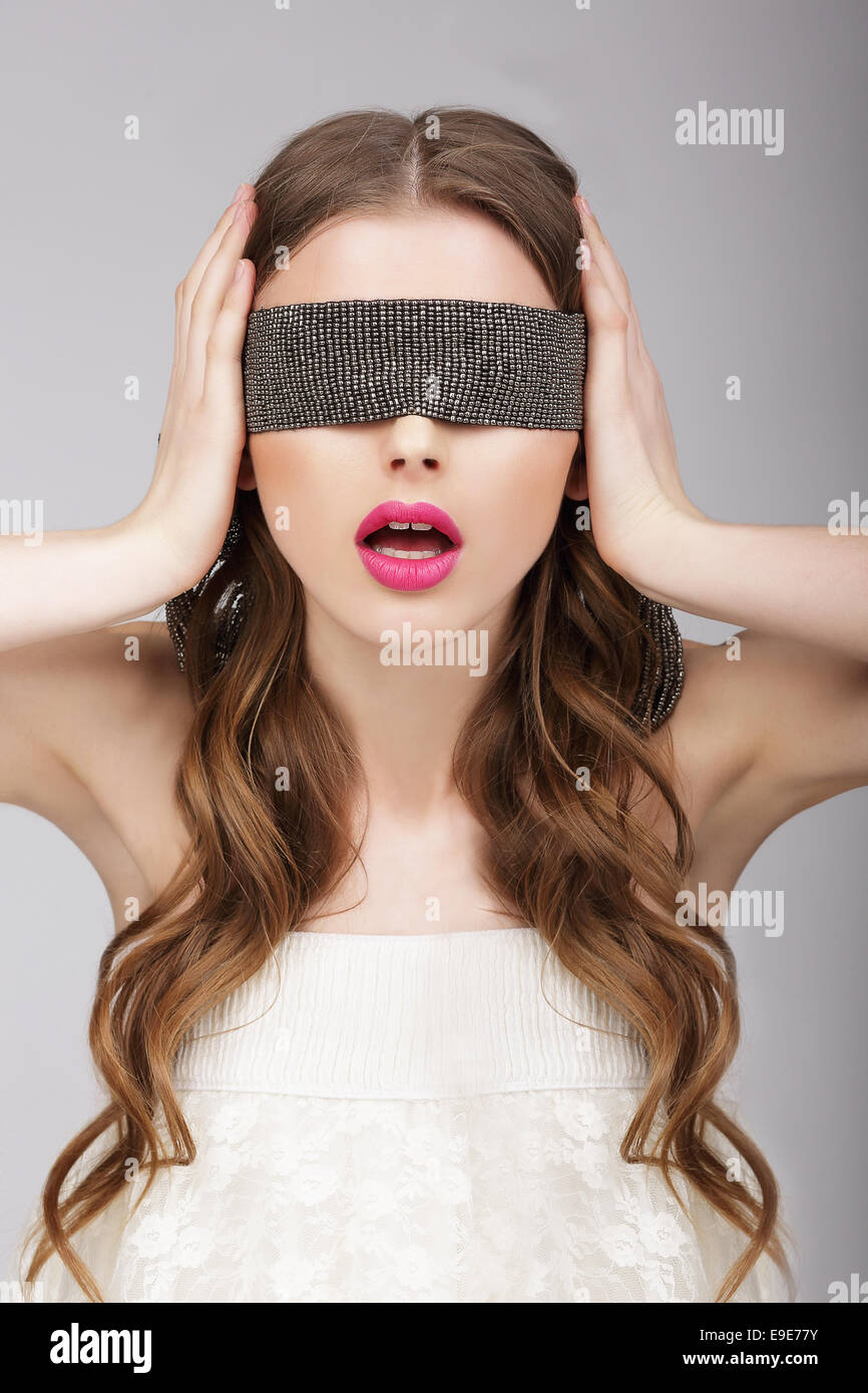 Confusion. Woman holding Headband on her Head - Stock Image