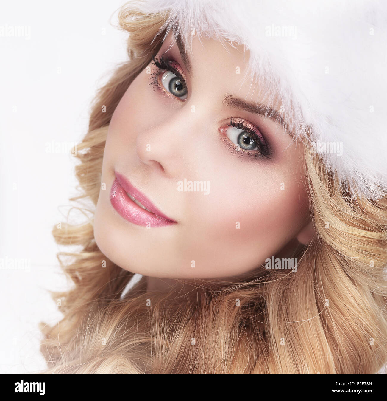 Cute Young Woman in Furry White Cap - Stock Image