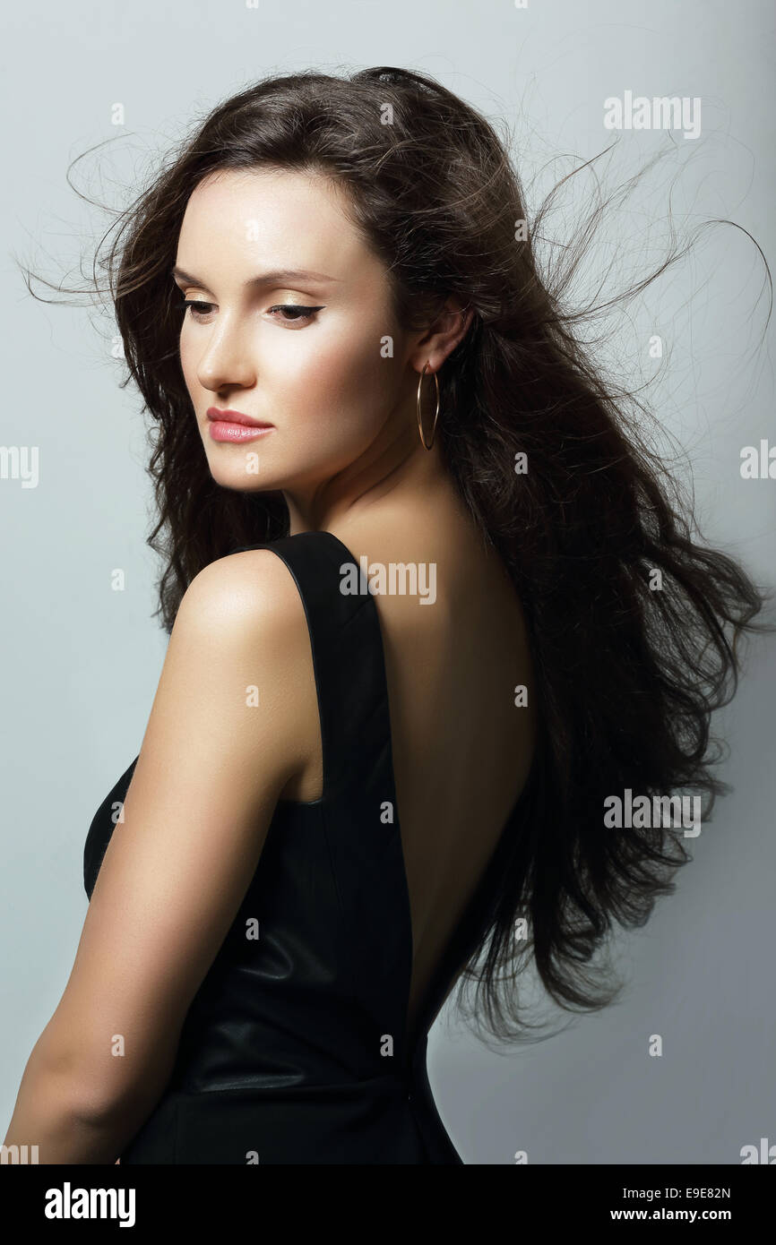 Charm. Aristocratic Lady in Black Dress and Flowing Hair - Stock Image