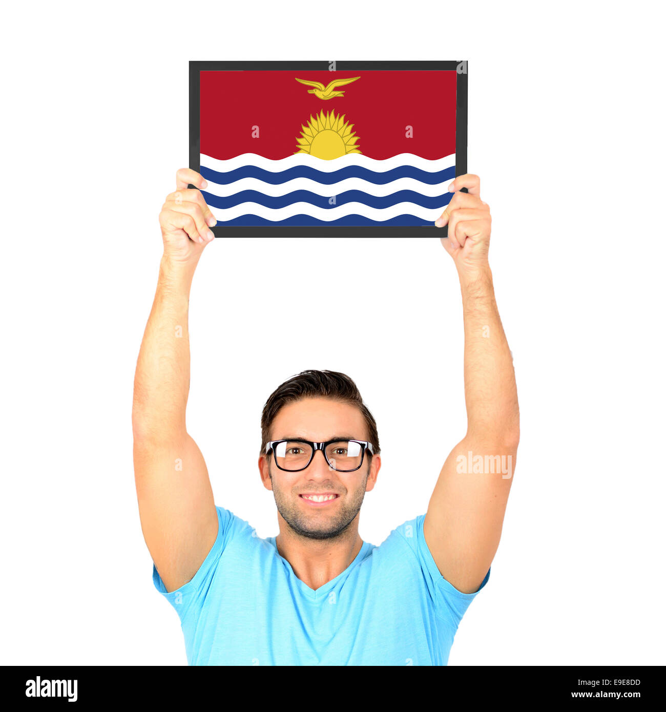 Portrait of a young casual man holding up board with National flag of Kiribati - Stock Image