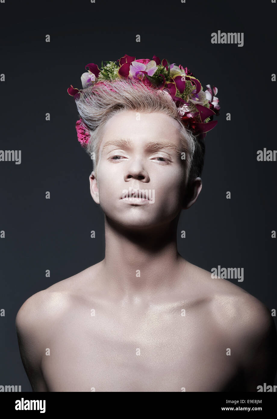 Beauty. Young Man with Wreath of Flowers over Gray - Stock Image