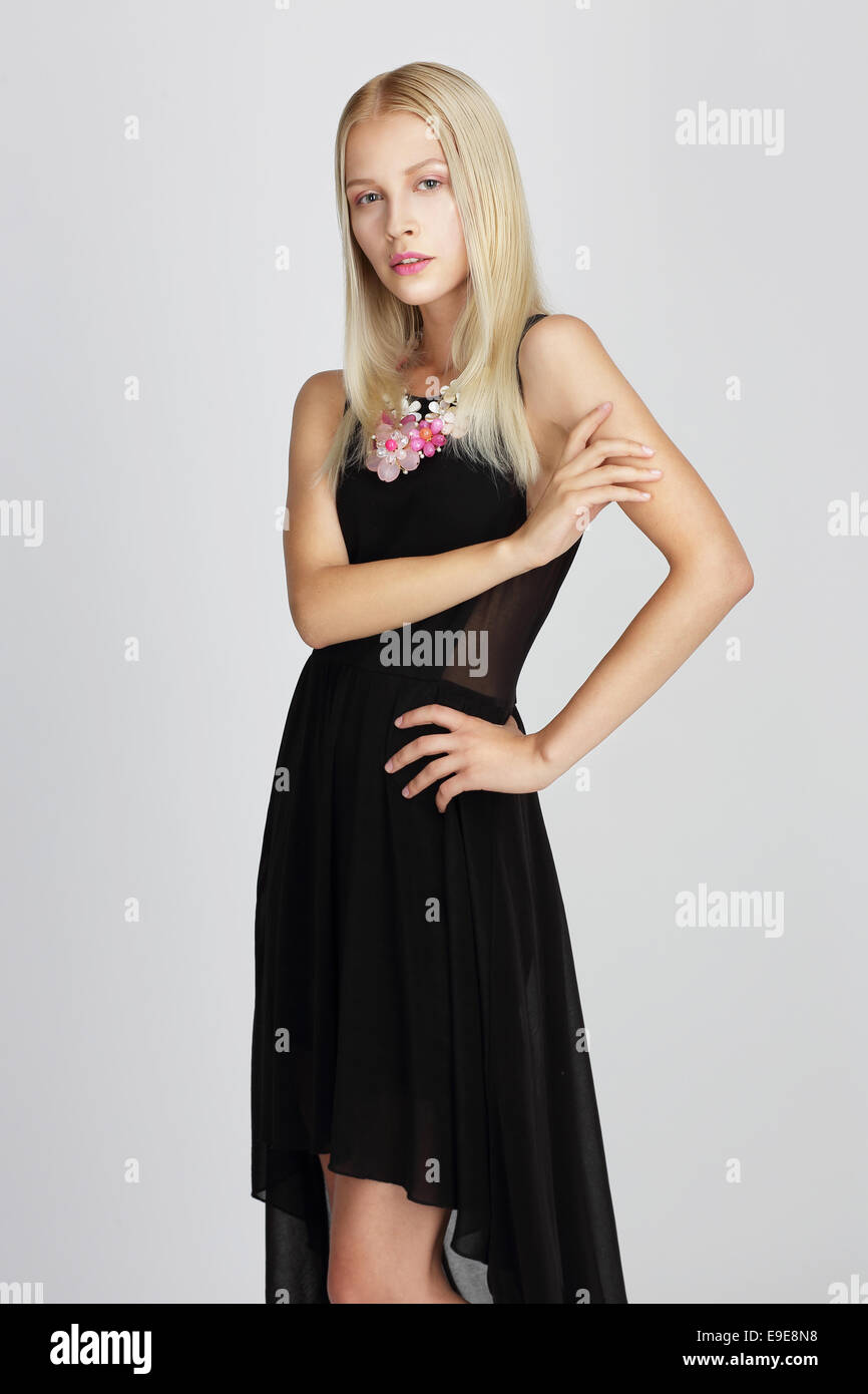 Sophisticated Lady in Black Silky Evening Dress Gracefully Posing - Stock Image