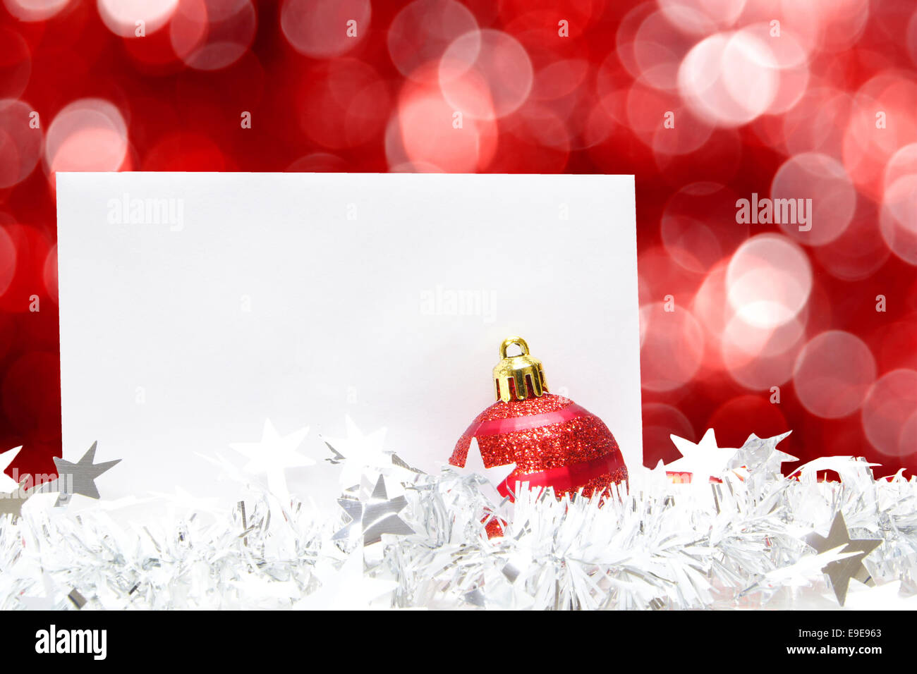 Blank white Christmas greeting card with bauble, garland and twinkling red background - Stock Image