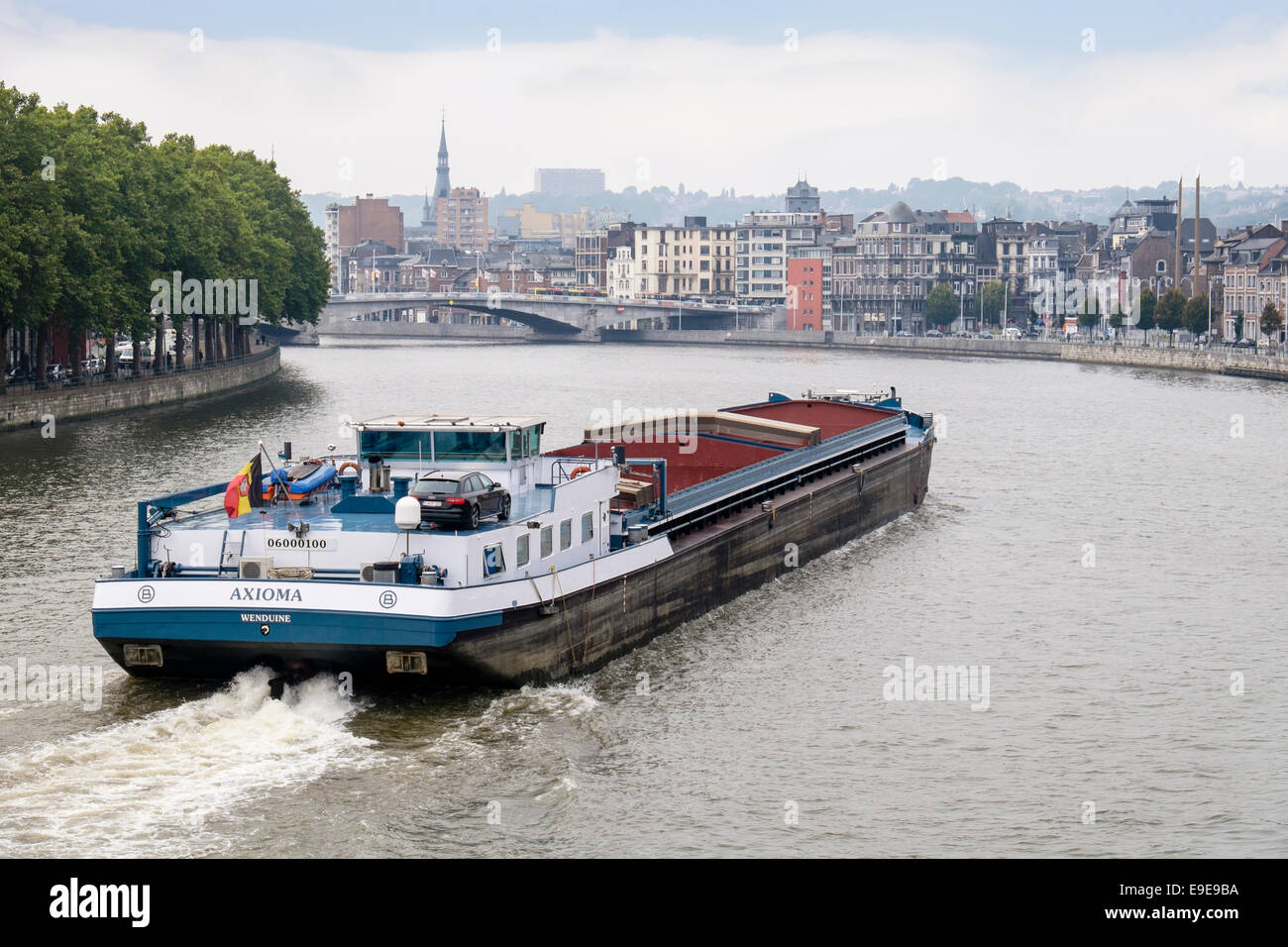 Cargo barge sailing along the River Meuse in Liege, Wallonia, Belgium, Europe - Stock Image