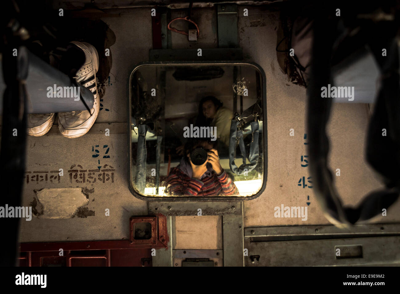 Woman taking pictures with her SLR camera in front of a mirror of a sleeper class coach in an Indian train - Stock Image