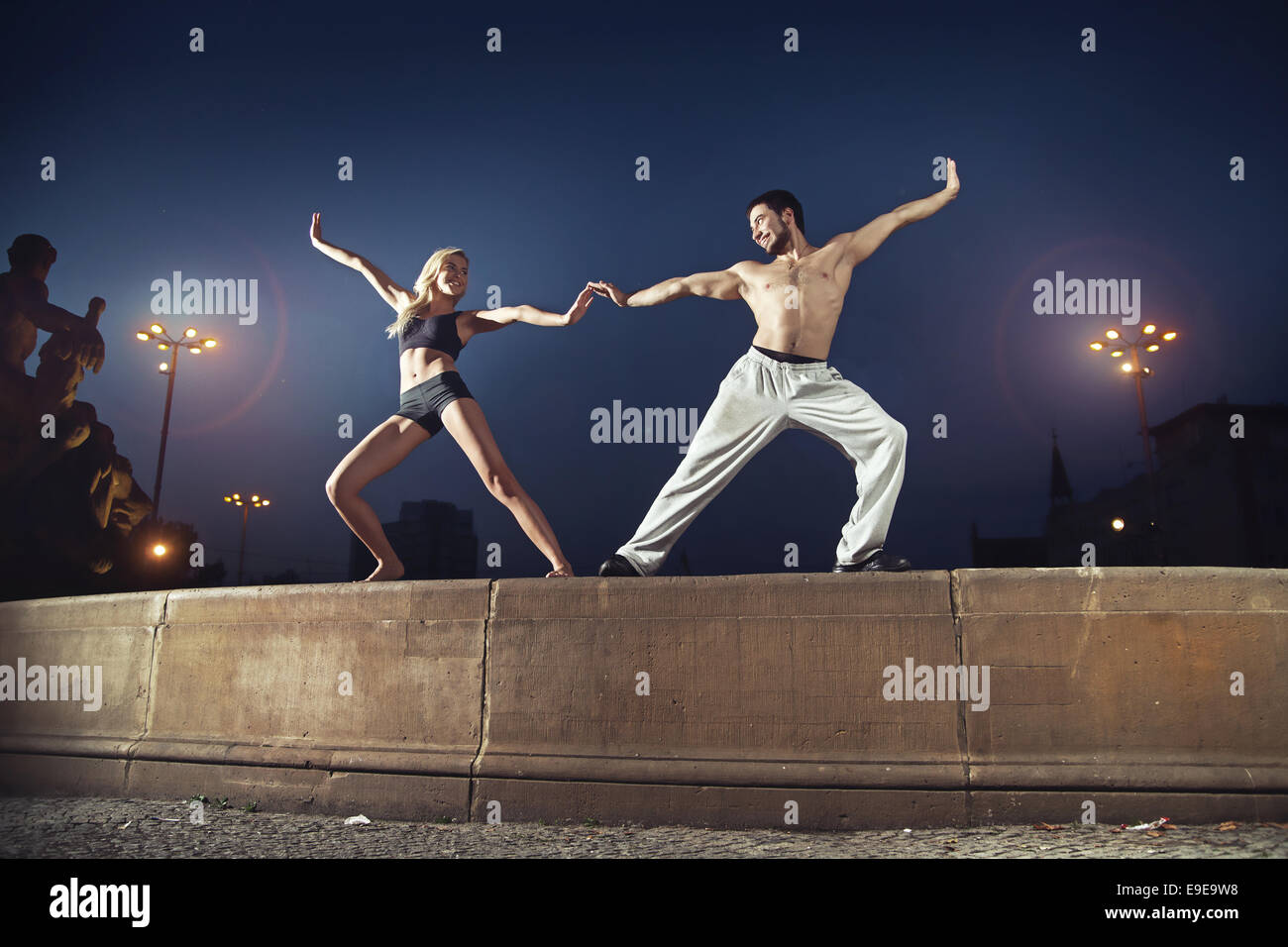 Two cheerful athletes practicing in the night - Stock Image